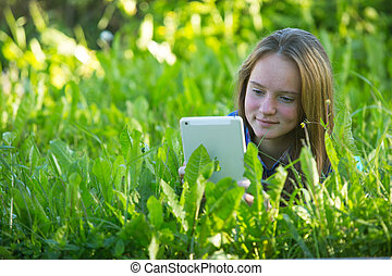 Beautiful young girl with a tablet PC lying in the grass.