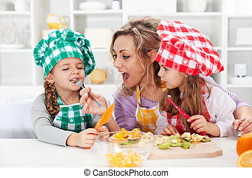 Woman and little girls preparing a fruit salad