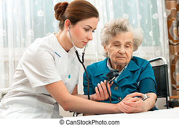measuring blood pressure of senior woman
