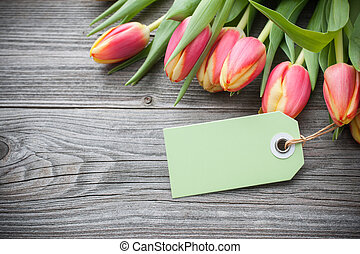 fresh tulips and tag with copy space on wooden background