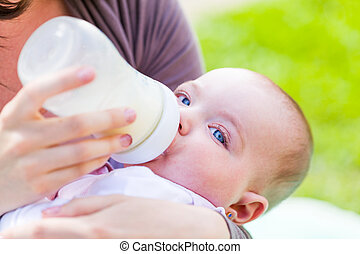 Baby feeding - Young mother feeding her baby with milk...
