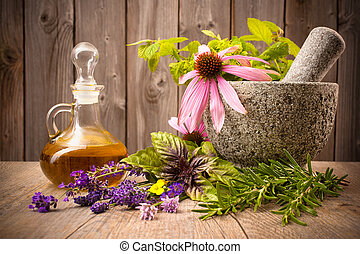 Healing herbs with mortar and bottle of essential oil on...