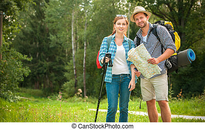 Hiking couple - Happy couple going on a hike together in a...