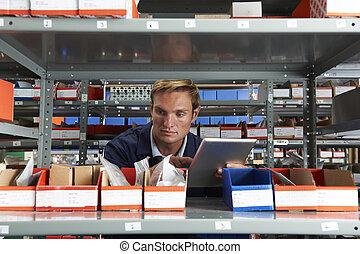 Factory Worker Using Digital Tablet In Store Room