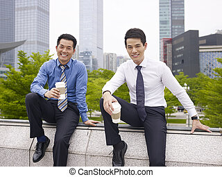 asian colleagues - two asian business executives talking in...