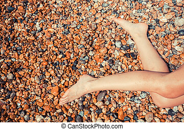 Legs of a young woman on a pebble beach