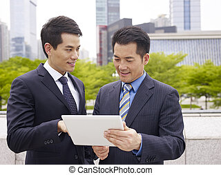 asian colleagues using ipad - asian business executives...