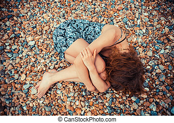Young woman lying on a pebble beach