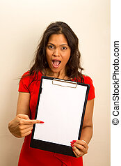 young woman looking surprised showing a clipboard.