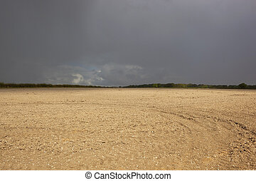 chalky soil and dramatic sky - a newly plowed field with...