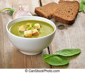 Spinach soup with dried crusts on wooden table