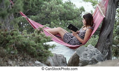 Girl in hammock e-book reading - Lying in hammock girl...