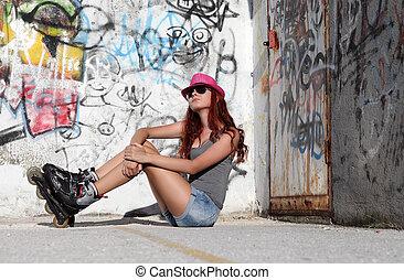 sitting girl with roller skates on graffiti background