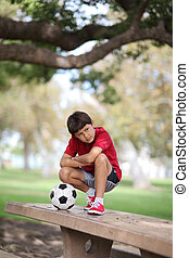Young boy in the park with ball