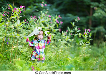 Funny baby girl playing peek a boo in a park under huge...