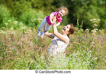 Young pregnant mother playing with her toddler in a sunny meadow