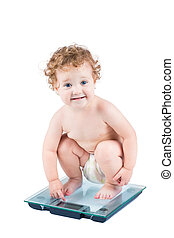 Cute baby girl on a weight scale, isolated on white