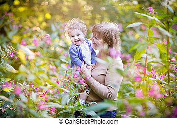 Beautiful woman playing with a laughing baby girl on sunset