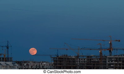 The moon in the sky over a building site