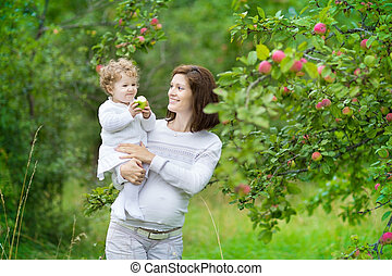Beautiful young pregnant woman and her laughing baby...