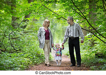 Young active grandparents hiking with their baby grand...