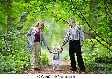 Young grandparents walking with their baby granddaughter in a pa