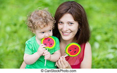 Beautiful young mother and her funny baby daughter eating...