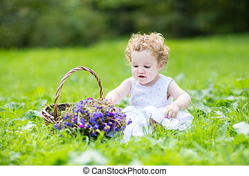Beautifu baby girl with blond curly hair wearing a white...
