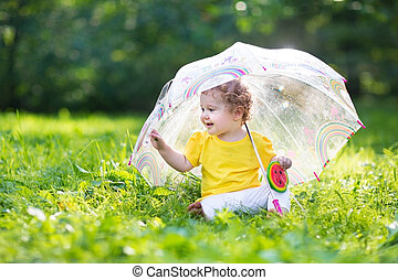 Cute little baby girl playing in the garden under an...