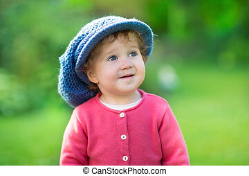 Funny baby girl wearing a big knitted hat playing in a sunny...