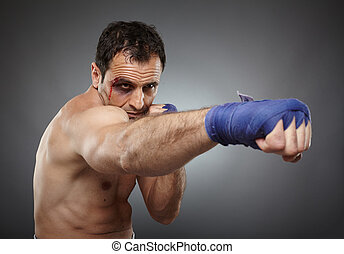 Bruised fighter punching - Muay thai or kickbox fighter with...