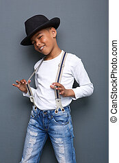 Cool kid smiling with hat and suspenders - Portrait of a...