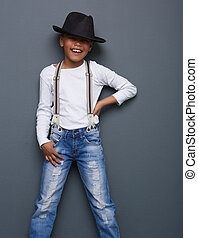 Portrait of a funny kid smiling with hat on gray background