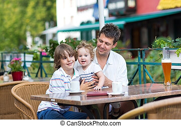 Young father enjoying a meal with his son and baby daughter in a