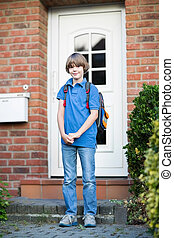 Cute student boy leaving home on his way to the first day at...