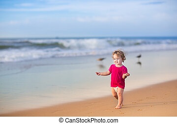 Beautiful baby girl with curly hair wearing a pink shirt and...