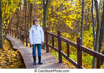 Cute school boy walking in a park on a wooden path way...