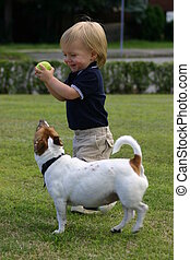 Cute blond Boy, one year old and his pet dog playing catch,...