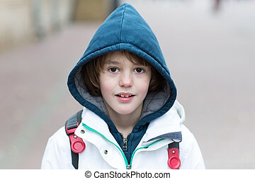 Cute boy on his way to school on a cold winter day