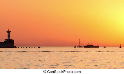 Boats floating on the sea at sunset