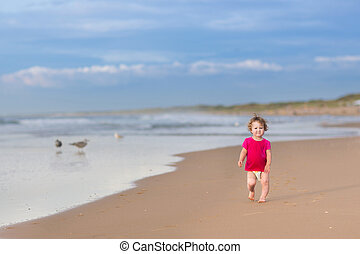 Cute funny baby girl running on a beautiful beach on a sunny...