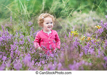 Beautiful little baby girl walking in purple autumn flowers...