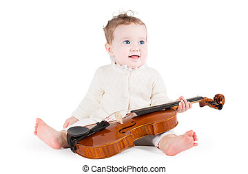 Funny little baby girl playing with a big violin on white...