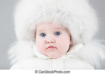 Funny little baby girl wearing a huge fur hat and a white...