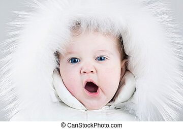Cute yawning baby girl wearing a huge white fur hat and a...