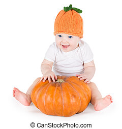 Sweet laughing baby girl playing with a huge pumpkin wearing...