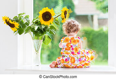 Baby girl next to sunflower bouque - Cute curly baby girl...