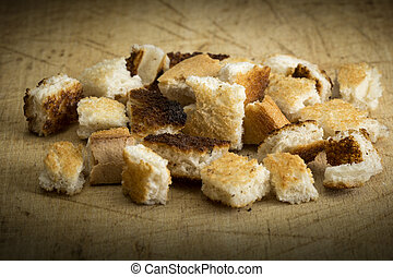 Crispy croutons on a wooden background
