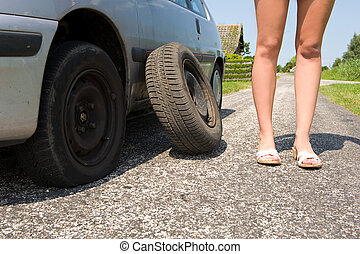 Flat tire - Long legged woman standing next to her car with...