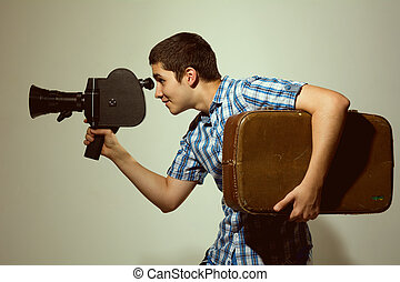 Young gay filmmaker with old movie camera and a suitcase in...